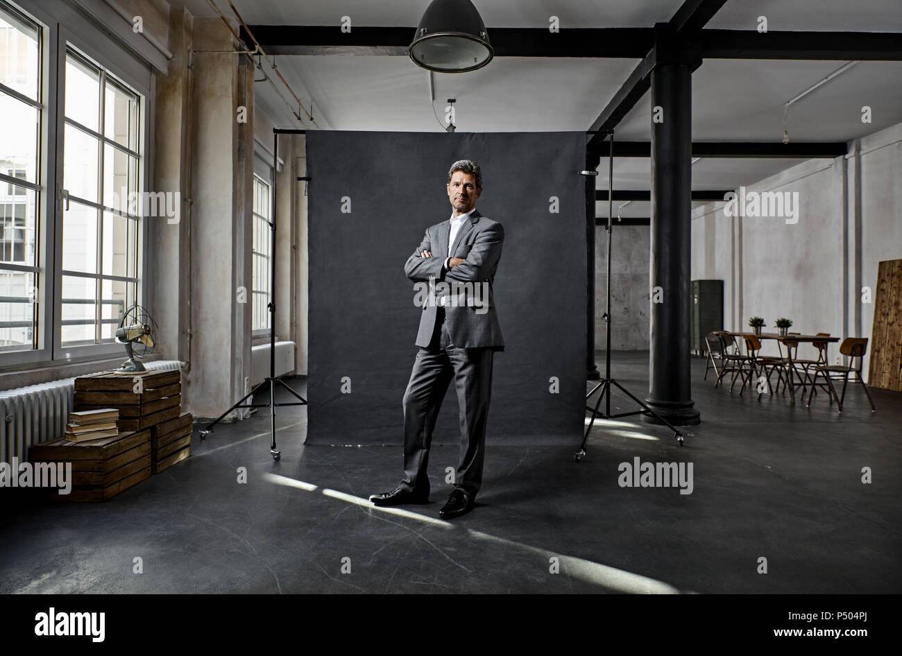 Portrait von Reifen Geschäftsmann vor schwarzem Hintergrund auf dem Dachboden Stockbild