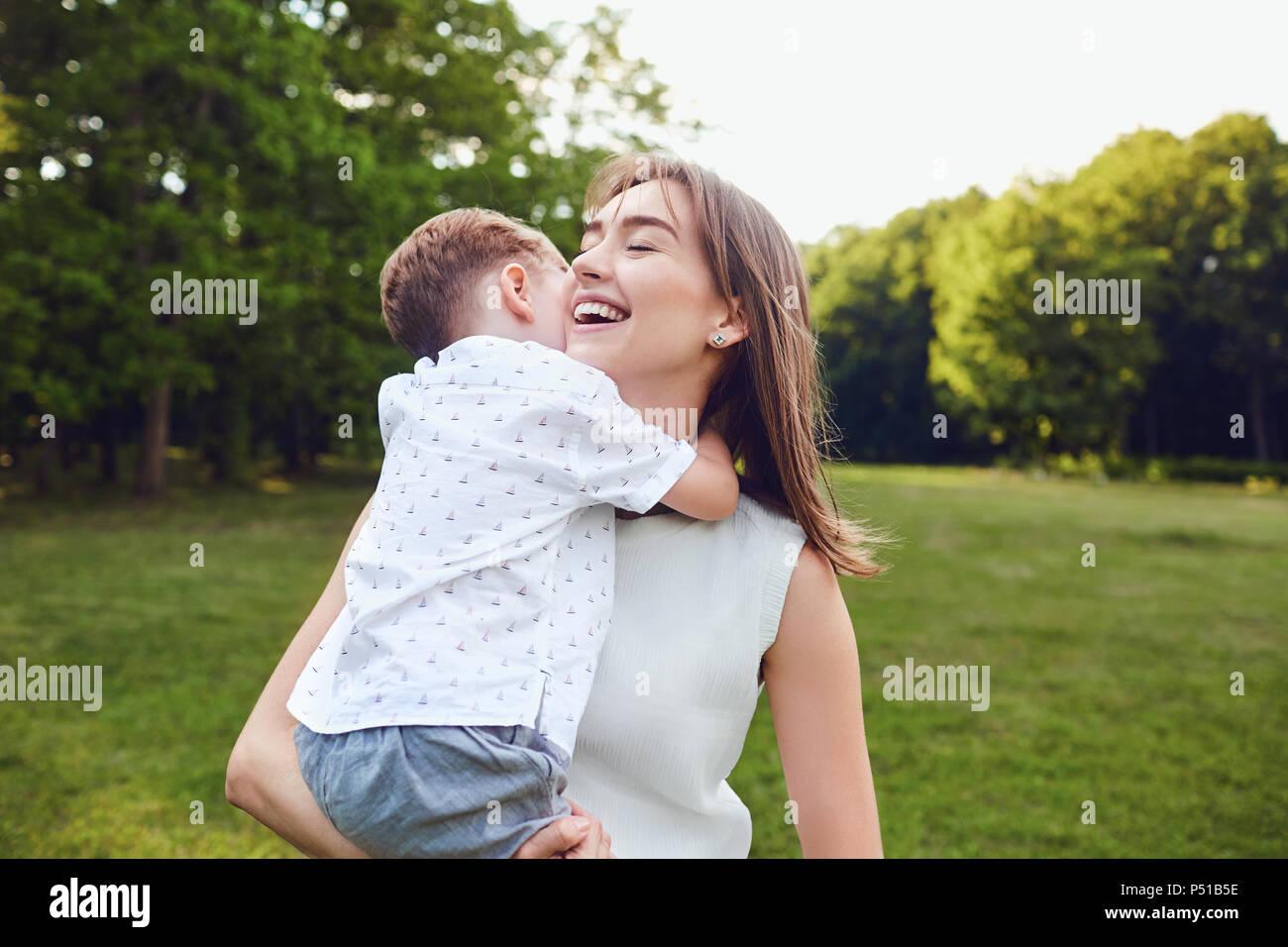 Mutter und Sohn umarmen im Park. Stockbild