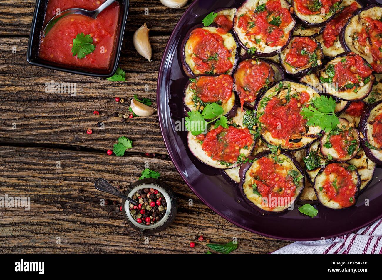 Auberginen gegrillt mit Tomatensauce, Knoblauch, Koriander und Minze. Veganes essen. Gegrillte Aubergine. Ansicht von oben. Flach Stockbild