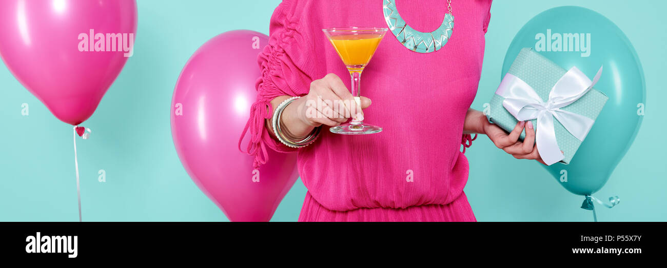 Wunderschöne junge Frau in party Outfit holding Geburtstagsgeschenk und Cocktail, über Pastell blau gefärbten Hintergrund. Geburtstag Banner. Stockbild