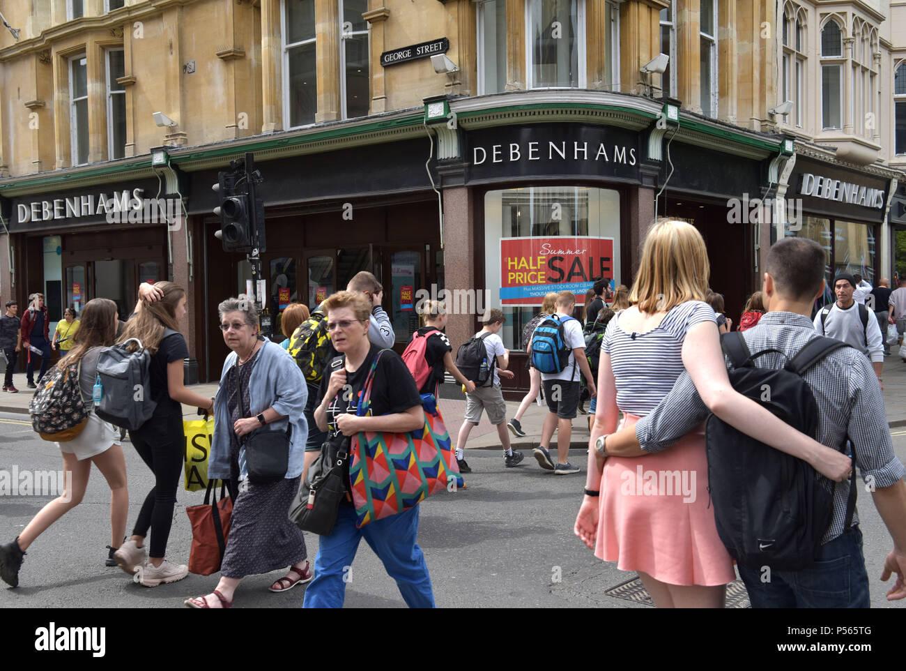 Käufer und Touristen zu Fuß vorbei am Kaufhaus Debenhams an der Ecke der High Street, George Street in Oxford. Stockbild