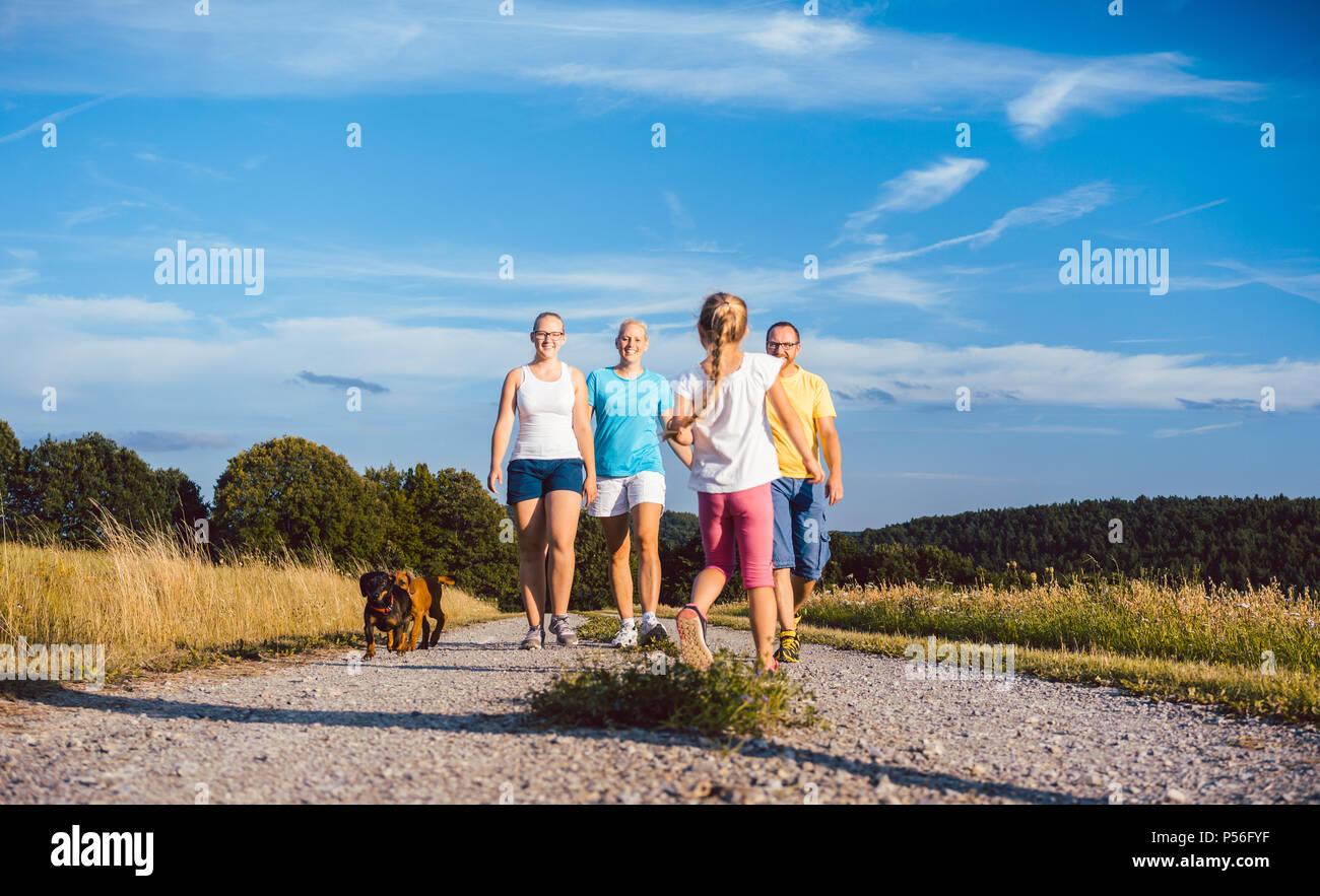 Familie wandern ihren Hund auf einem unbefestigten Pfad Stockbild