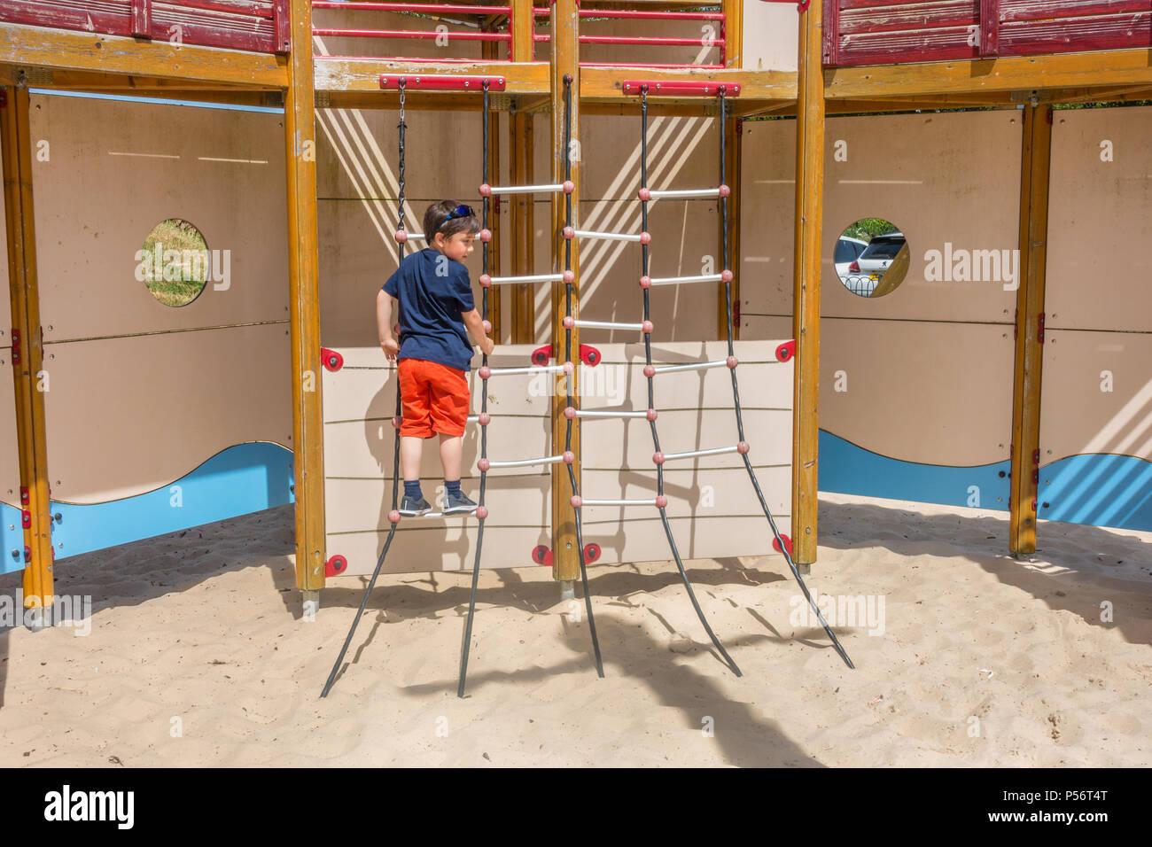 Klettergerüst Hängebrücke : Ein kleiner junge steigt auf einem klettergerüst dem