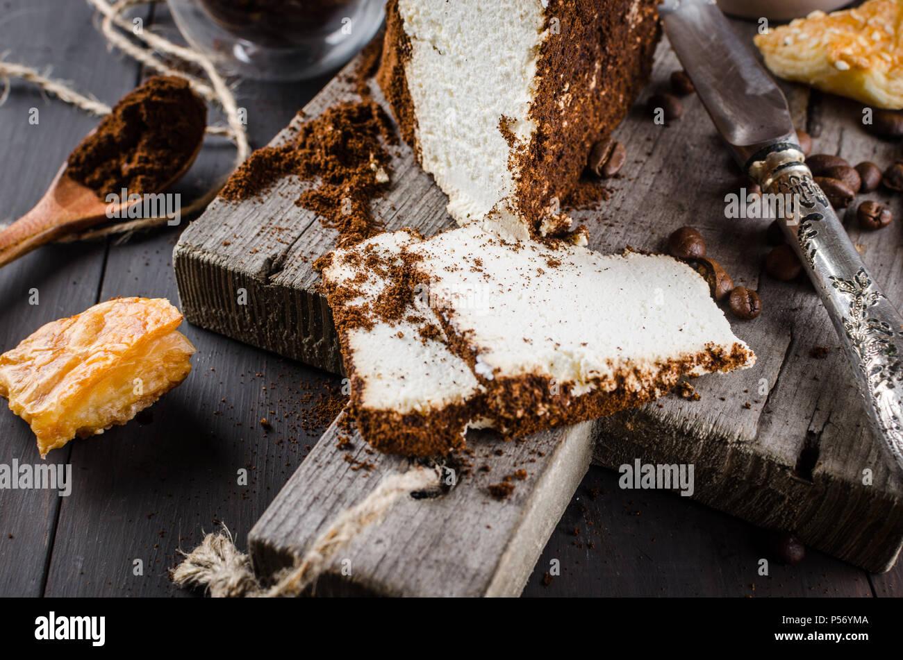 Weiche hausgemachten Käse in gemahlenen Kaffee und eine Tasse Kaffee mit Milch Frühstück auf einer hölzernen Tisch gewickelt Stockbild