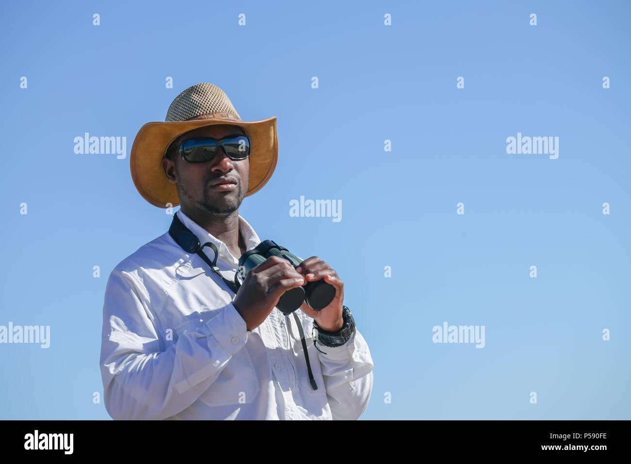 Afrikanische mann von safari fahrzeug trug hut und weißen shirt und