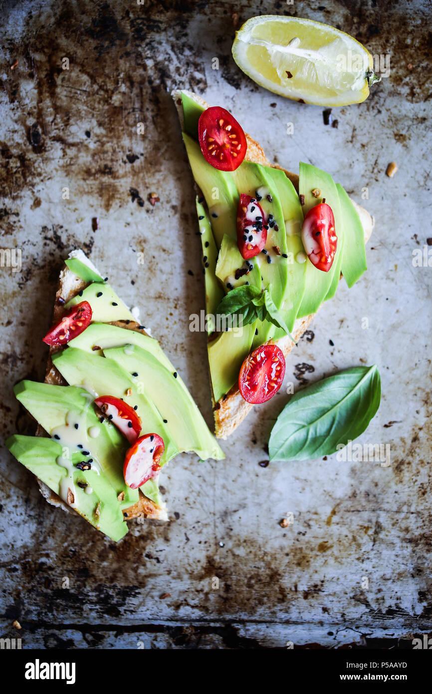 Eine einfache und köstliche avotoast mit Cherry Tomaten und tahini Sosse. Stockbild