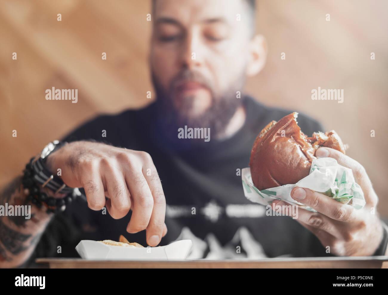 Junger bärtiger Mann essen Burger und Pommes frites. Stockbild