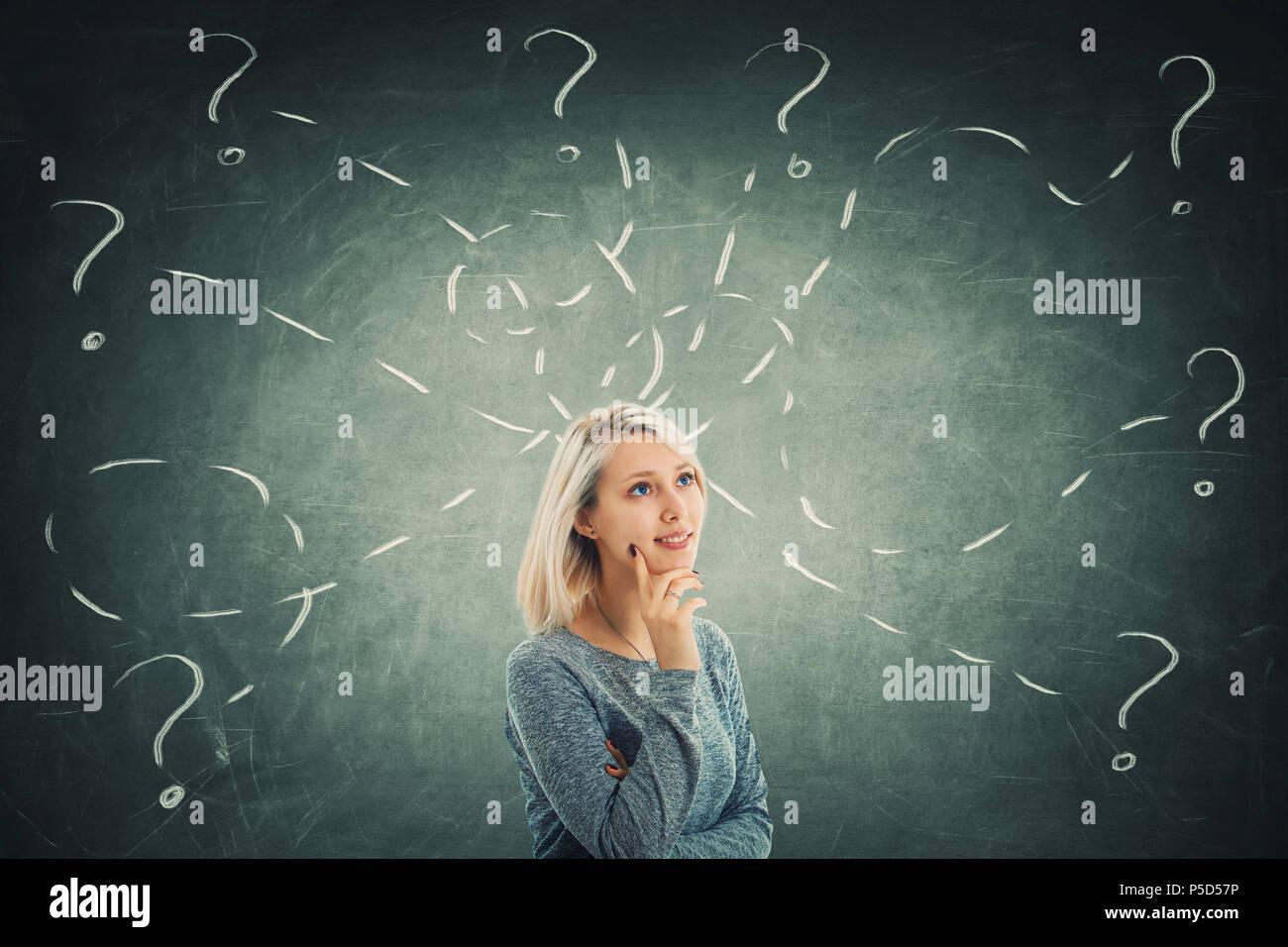 Junge Frau vor einer Tafel versuchen, verschiedene Aufgaben zu lösen Rätsel, eine Menge Fragen. Inspiration Konzept und Entwicklung. Stockbild