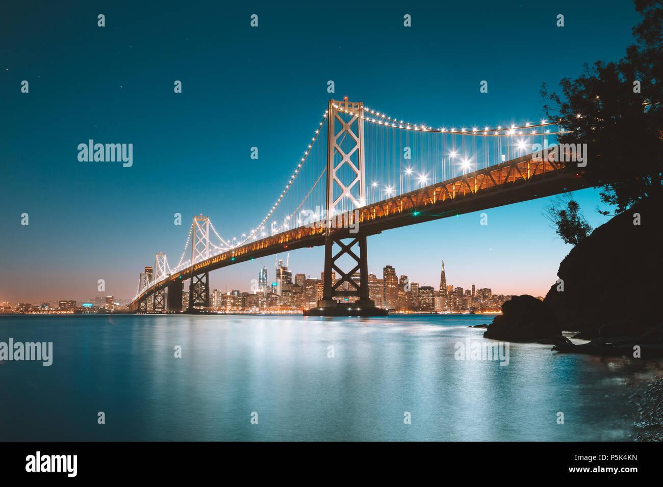 Klassische Panoramablick auf San Francisco Skyline mit berühmten Oakland Bay Bridge leuchtet in schönen Abend dämmerung Dämmerung im Sommer Stockbild