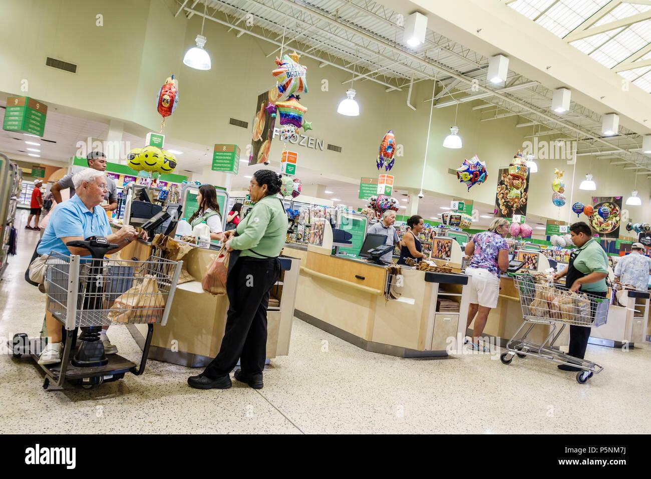 Naples Florida Publix Supermarkt Supermarkt elektrische Warenkorb gehbehindert Kassierer bagger Warenkorb Hispanic Mann Frau senior Custom Stockbild