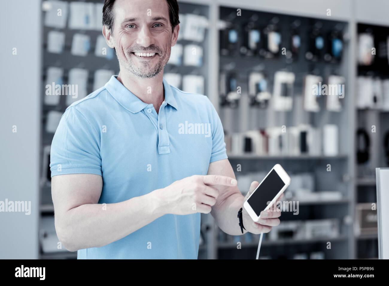 Glücklich lächelnde Mann an das Smartphone zeigt Stockbild