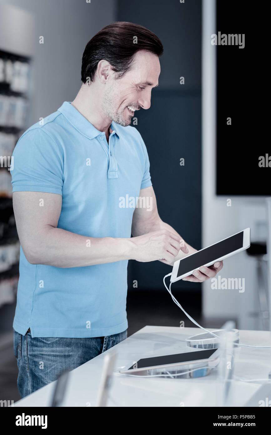 Ruhig lächelnd Mann die Wahl eines neuen Tablet Stockbild