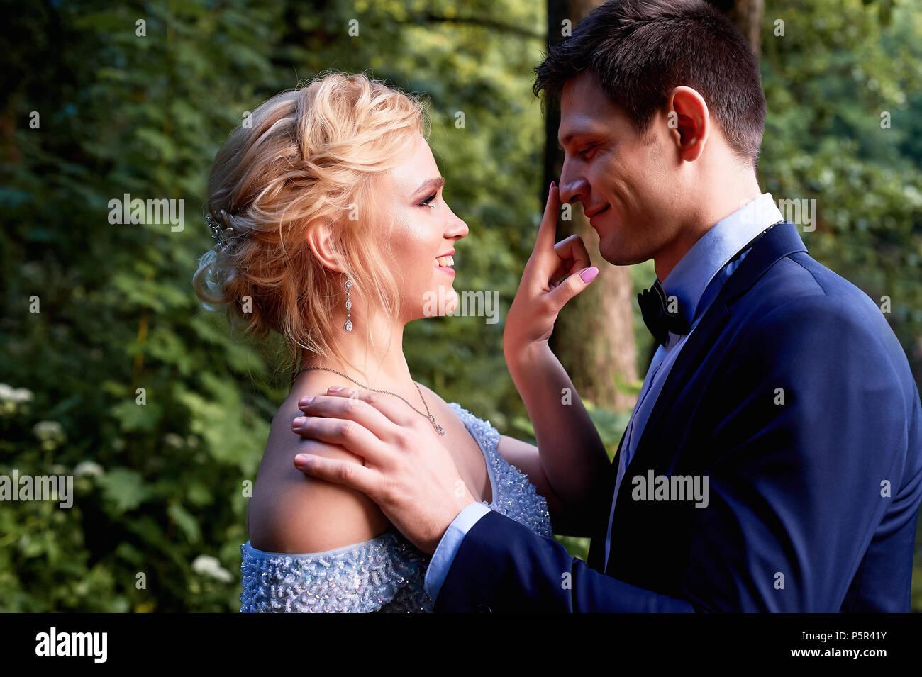 Die Braut sieht bei der Bräutigam im Scherz. Und mit einem Finger auf die Spitze seiner Nase berührte. Hochzeit gehen und Fotoshooting Stockbild