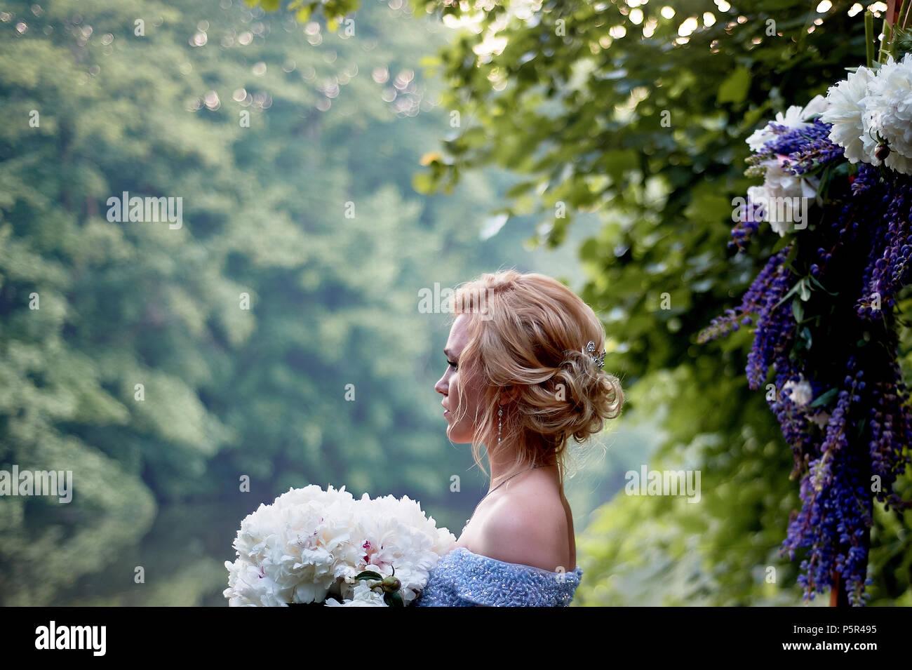 Die Braut steht bei den Bogen, mit Blumen geschmückt, mit einem großen Blumenstrauß aus den weißen Pfingstrosen. Registrierung vor Ort im Park Hochzeit gehen und Foto sh Stockfoto