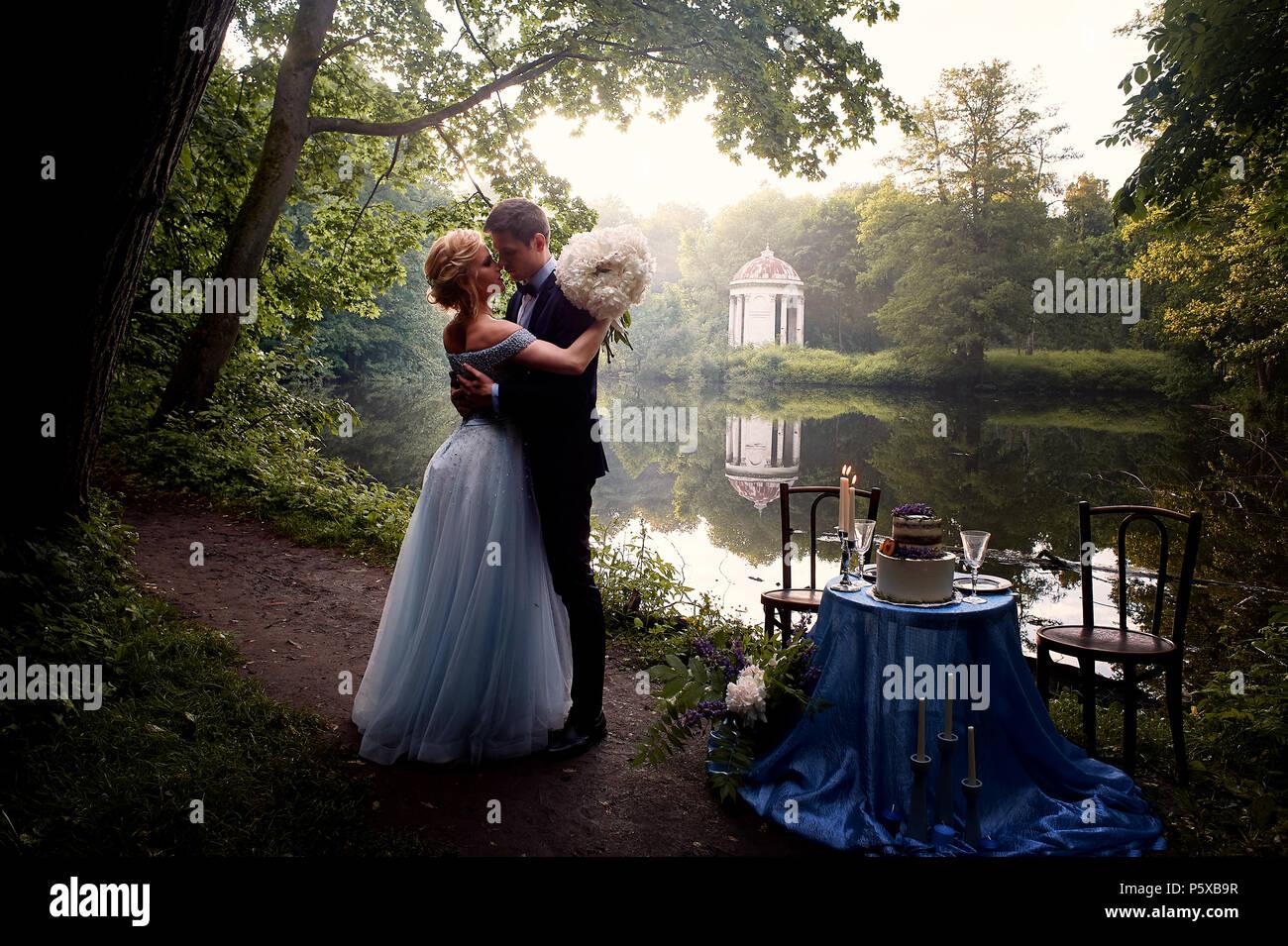 Die Braut und der Bräutigam stand neben einem malerischen See. Einrichtung in Blau Tönen, auf dem Tisch eine zweistufige Kuchen, Gläser und Kerzen. Romantische Hochzeit Abendessen. Stockbild