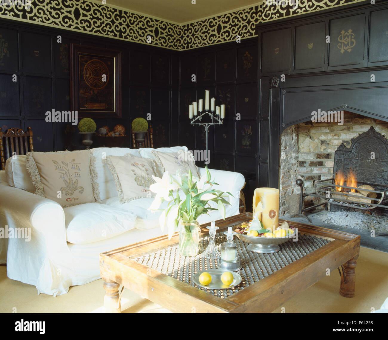 Weiß Sofa und indonesischen Holz Tisch vor einem Kamin mit ...