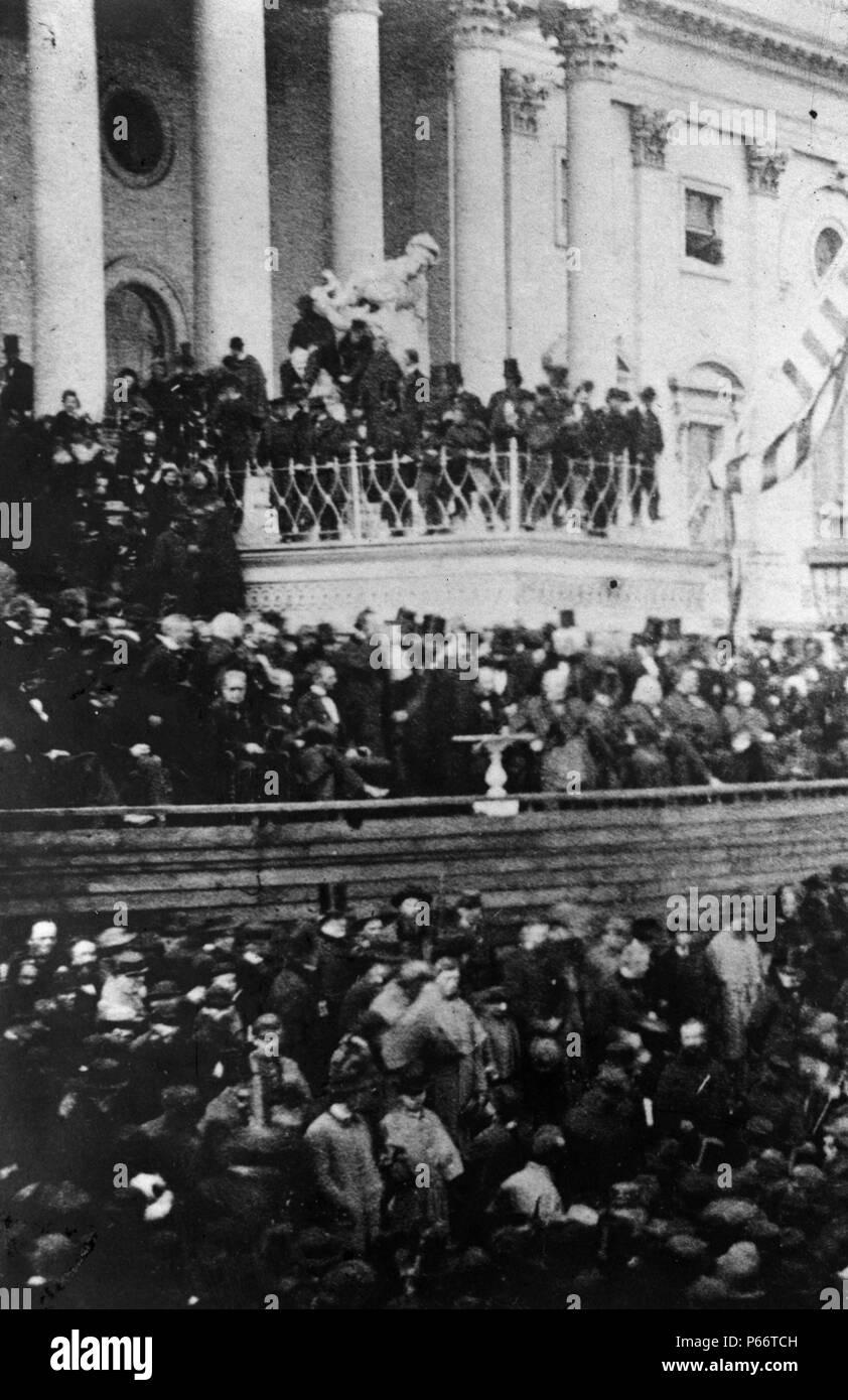 Präsident Abraham Lincoln mit seiner zweiten Antrittsrede vor der United States Capitol, März 4, 1865. Der Gast erwartet die Adresse des Präsidenten. Lincoln sitzt noch an der linken Mitte. Auf Lincoln's Links sind die Richter des Obersten Gerichts; zu seiner Rechten, die Mitglieder seines Kabinetts. An seinem sofort rechts, ist Andrew Johnson; und, neben Johnson und schaut in den Kameramann, ist der scheidende Vizepräsident Hannibal Hamlin. Stockfoto