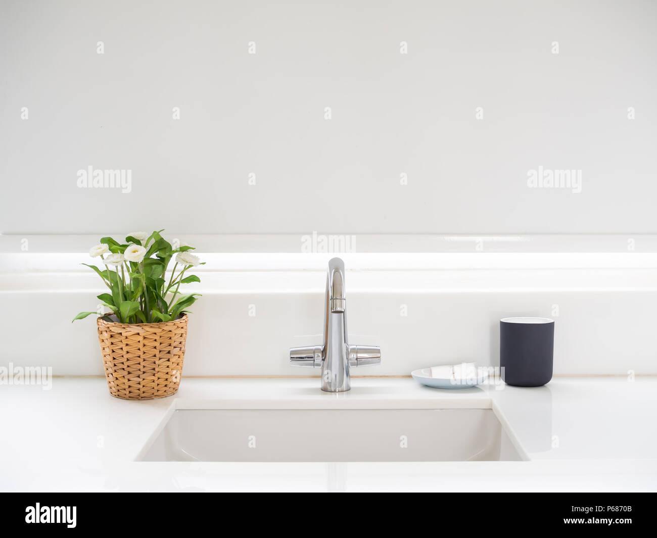 Sauberes weißes Bad mit Waschbecken Waschbecken Wasserhahn, Blumen ...