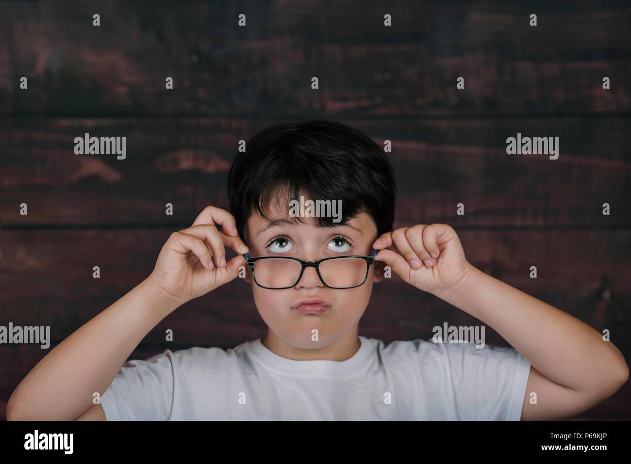 Junge mit Brille auf Holz- Hintergrund Stockbild