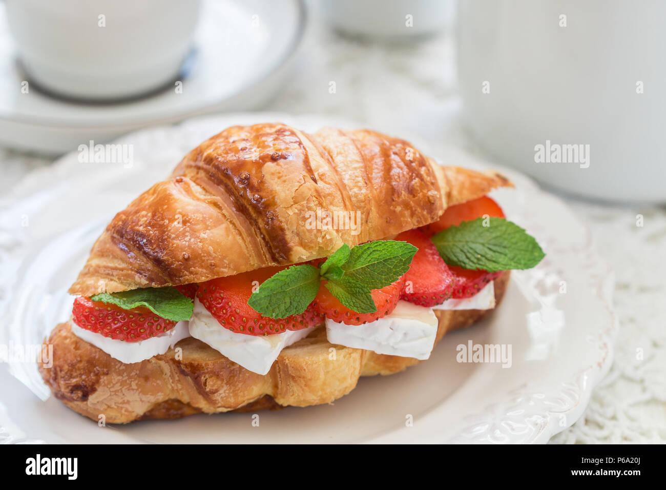 Croissant mit Erdbeeren, Brie Käse oder Camambert und Minze. Köstliches Frühstück. Selektiver Fokus Stockbild