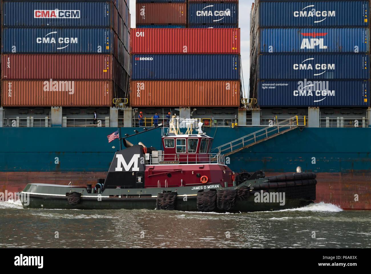 Moran Abschleppen des Traktors tug James D. Moran transfer unterwegs mit einem Container schiff mit Containern gestapelt Stockfoto