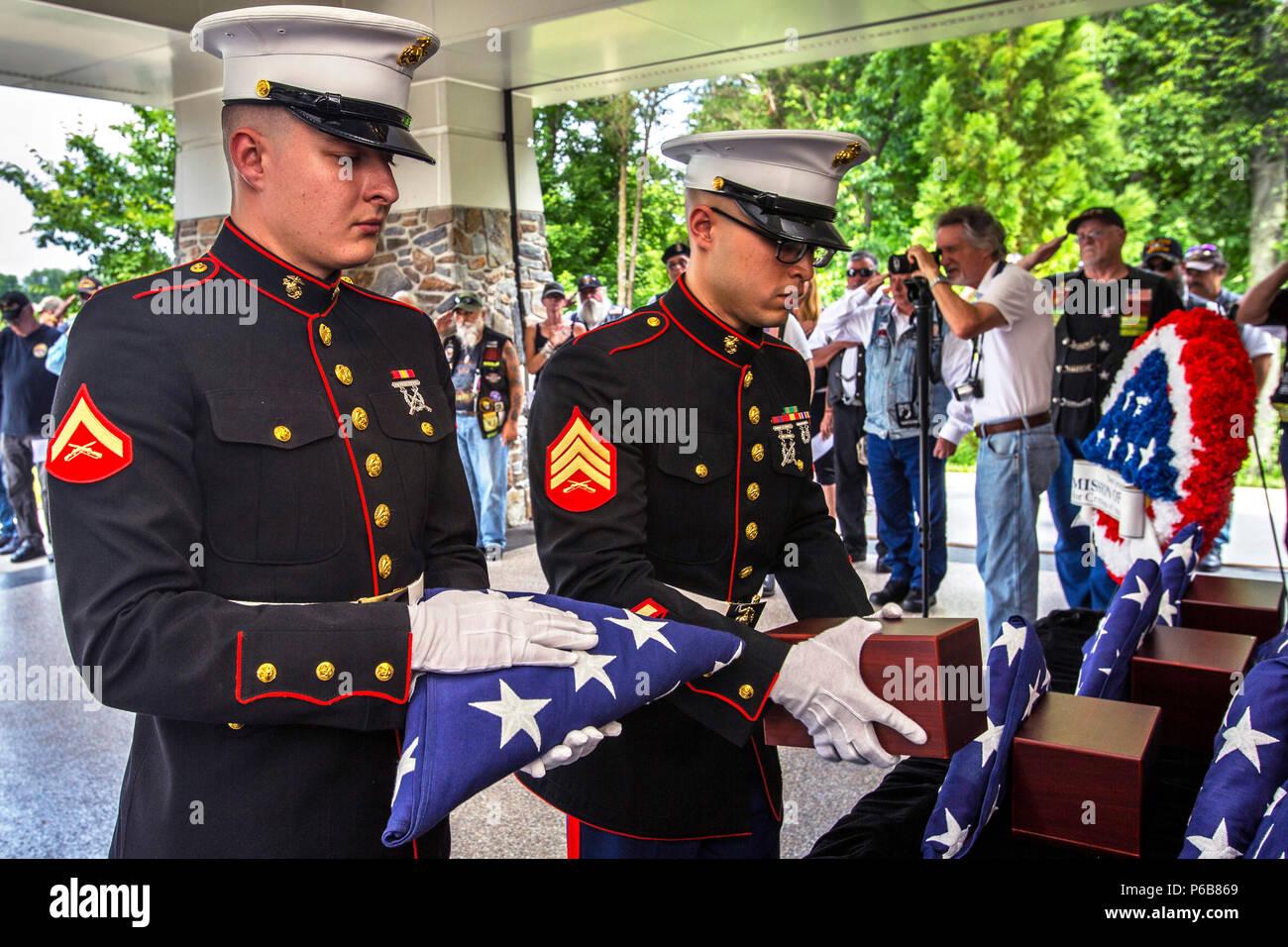 Us Marine Corps Sgt. Gregory Perez, rechts, legt eine Urne mit den cremains eines Veterans während Lance Cpl. Tyler Eichman-Cothern hält eine amerikanische Flagge während der 29 New Jersey Mission der Ehre (NJMOH) Zeremonie an der Brigadier General William C. Doyle Veterans Memorial Friedhof im Norden Hannovers Township, New Jersey, 21. Juni 2018. Die cremains von eine Welt krieg ich Veteran Joseph S. Bey, zwei Weltkriegveterane Arthur L. Hodges und James C. Warren, zwei Korean War Veterans Wilbur J. durchbohren und Claude Robinson, drei Vietnam Veteranen Joseph F. Boone jr., Malachia Rich Jr. und Wilbert E.S Stockbild