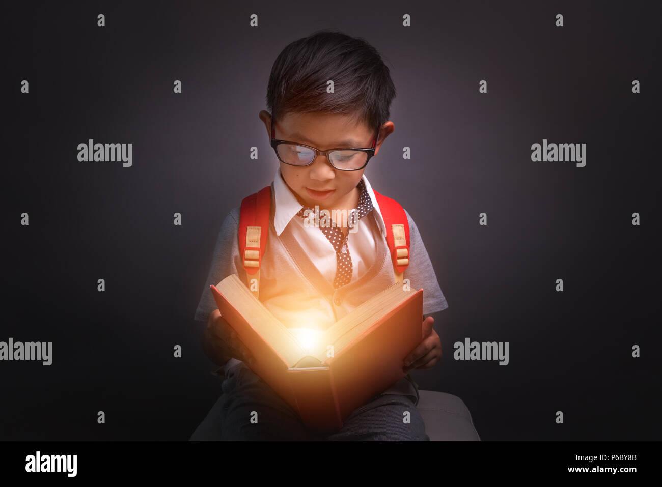 Zurück zu Schule, Kind eröffnet ein magisches Buch, das Bild dunkel Ton Stockbild