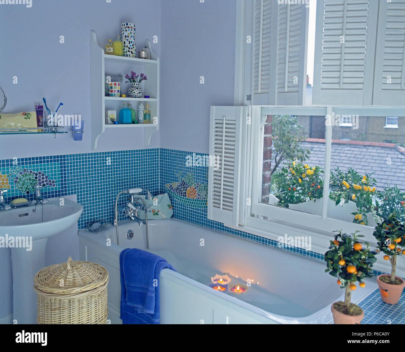 Schwimmende Kerzen in der Badewanne unter Fenster mit weißen ...