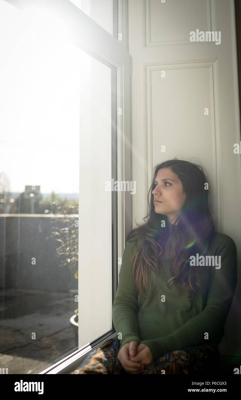 Frau auf der Suche durch das Fenster sitzend auf Fensterbank Stockfoto