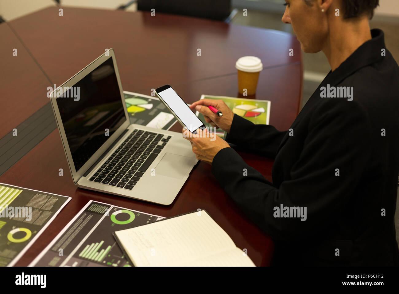 Reife Geschäftsfrau mit Handy am Schreibtisch Stockfoto