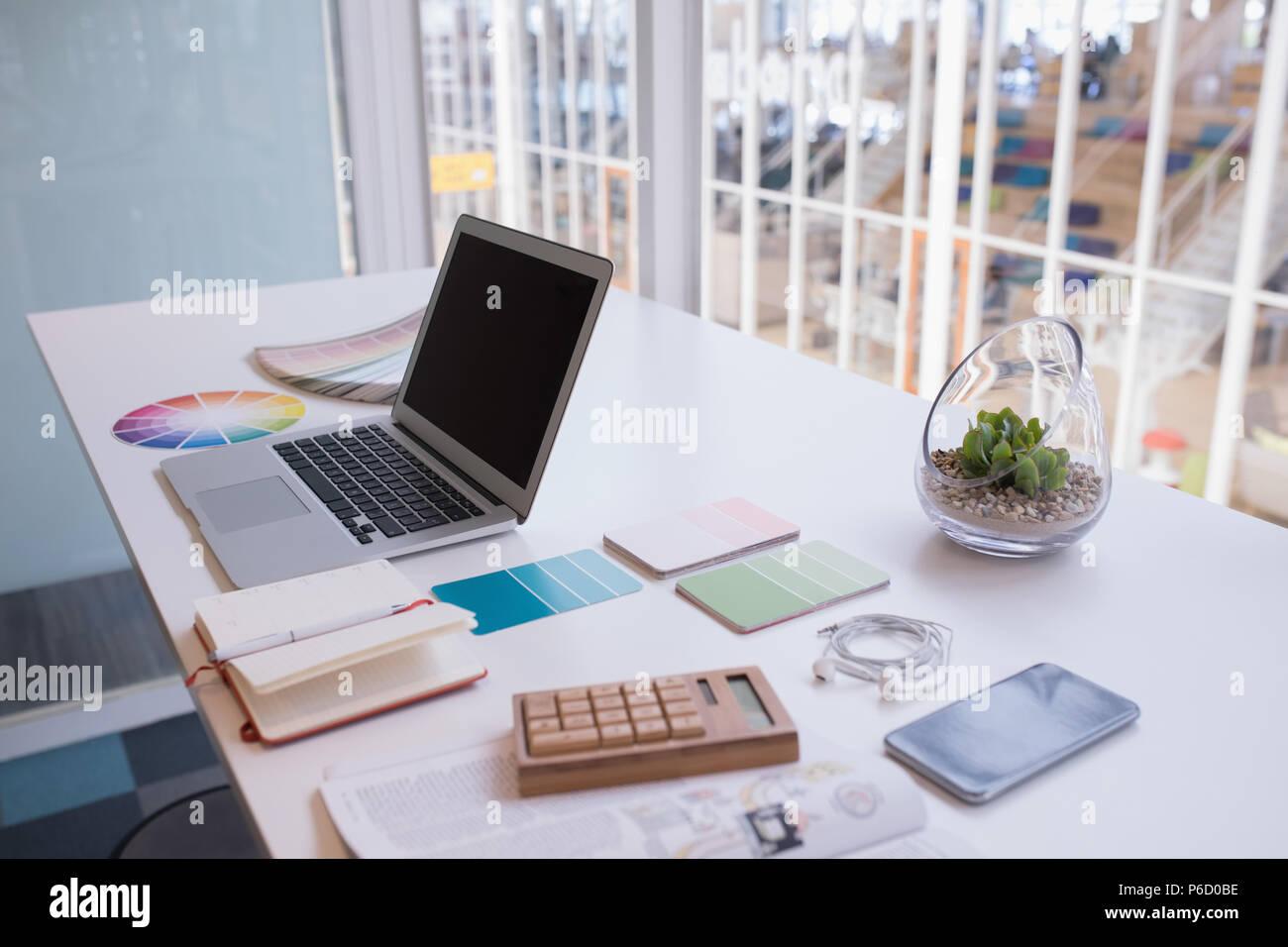 Laptop und Farbmuster am Schreibtisch Stockfoto
