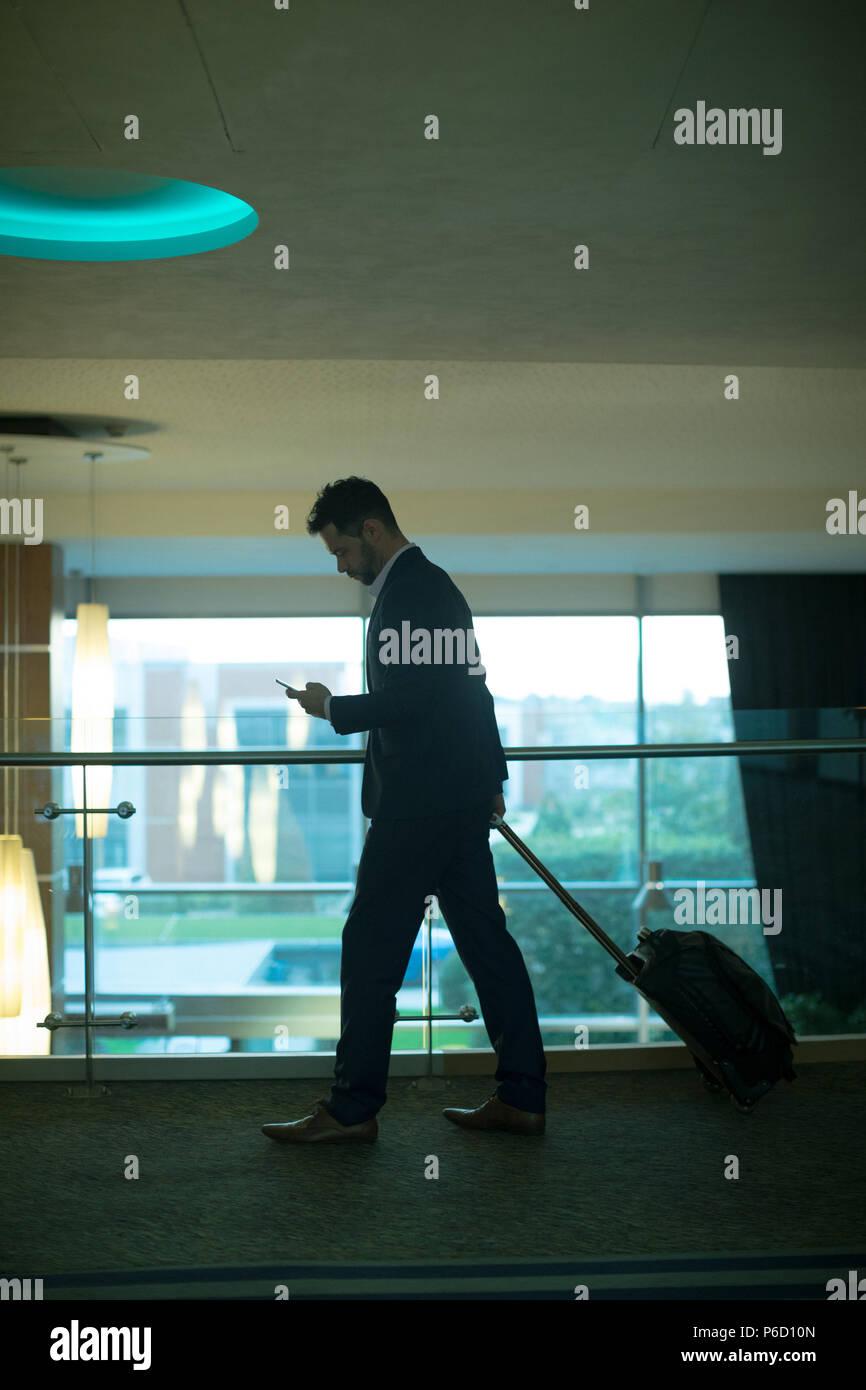 Geschäftsmann mit Mobiltelefon im Korridor Stockbild