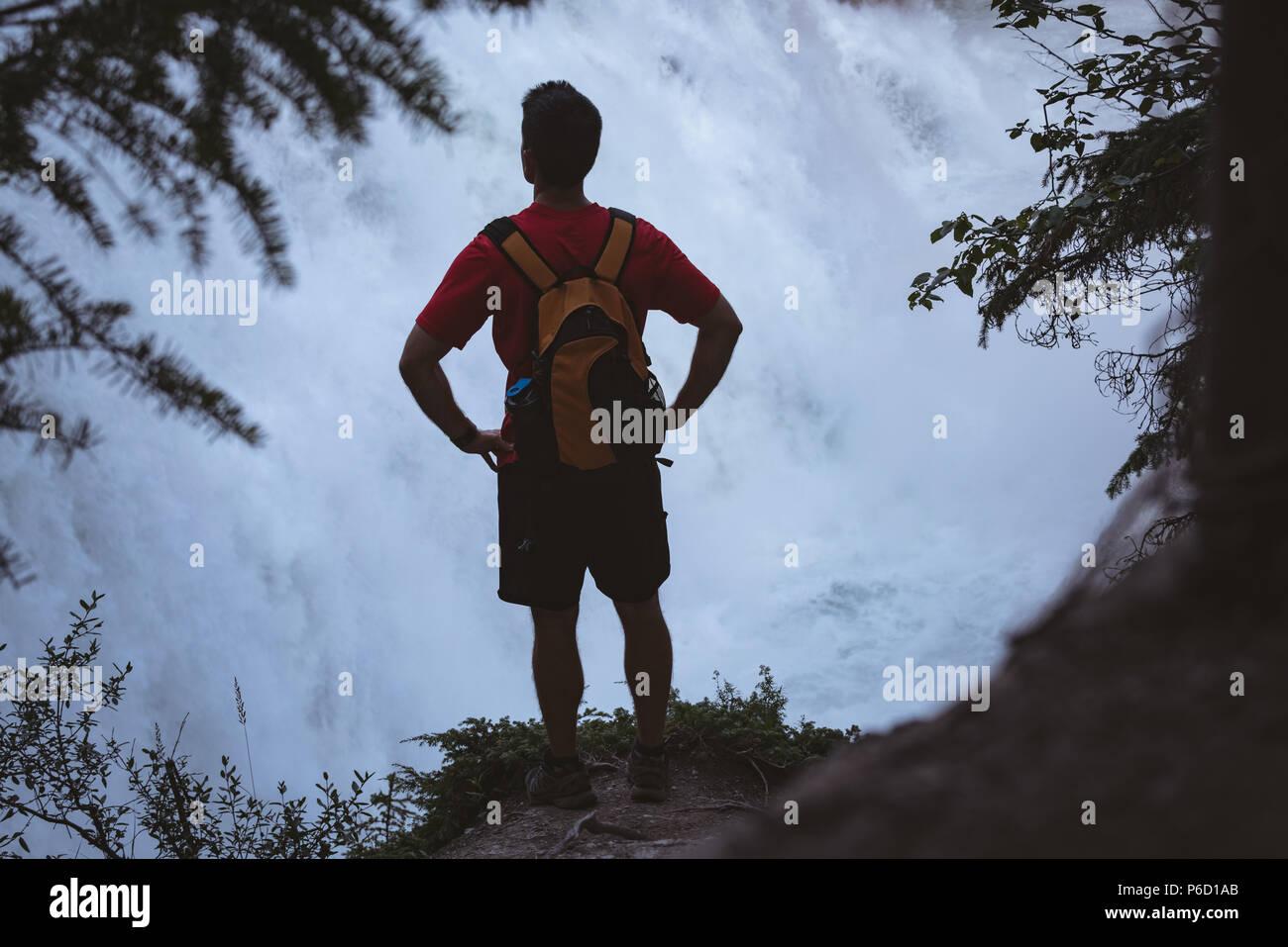 Mann stand mit den Händen auf der Hüfte in der Nähe von Wasserfall Stockfoto