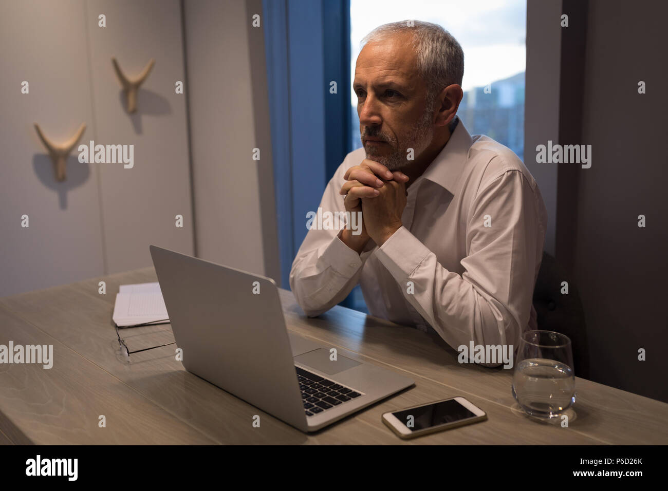Unternehmer denken tief, während am Schreibtisch sitzen Stockbild