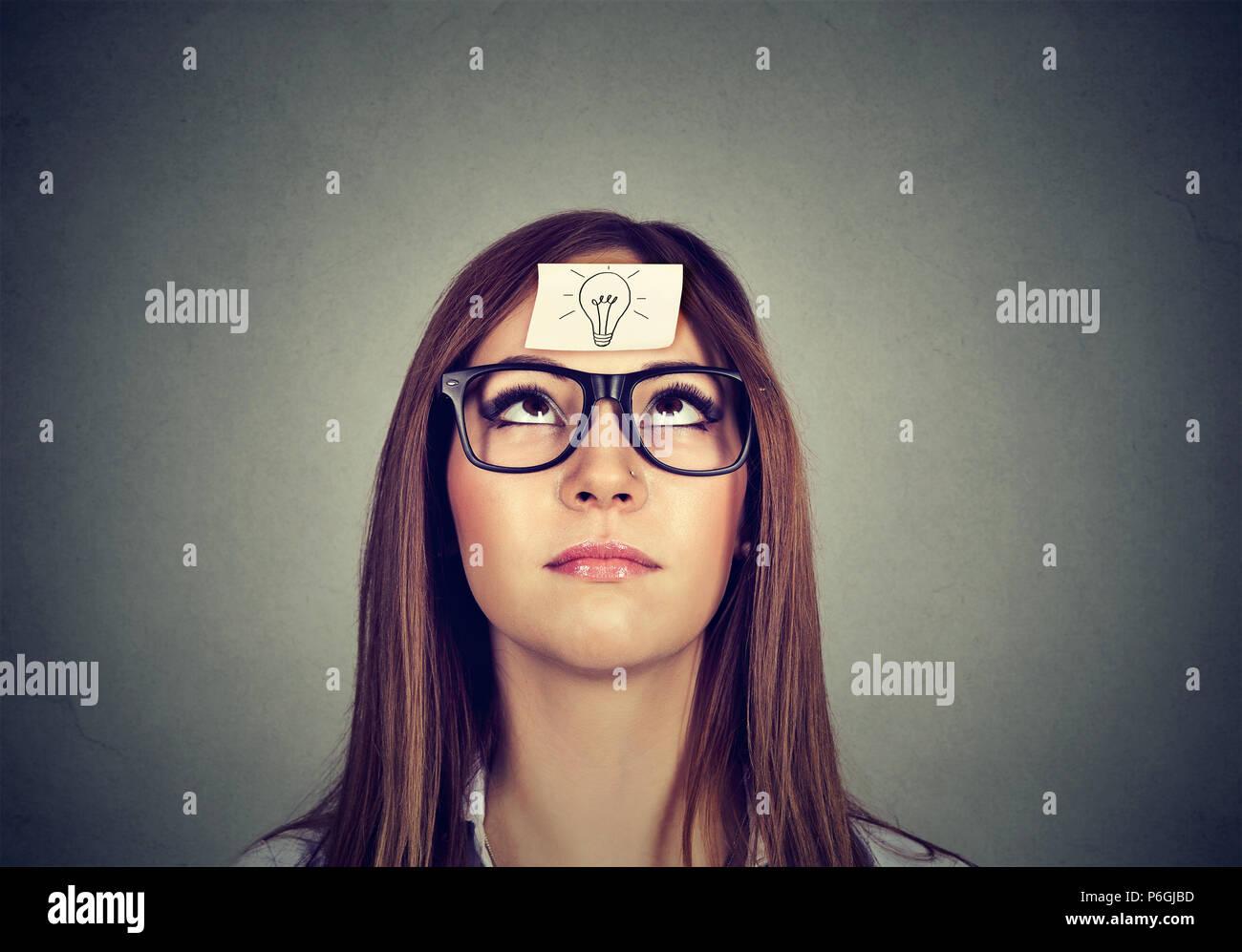 Junge Frau mit Aufkleber auf Gesicht mit Symbol der Glühbirne und die Suche nach Denken über Lösung Stockbild