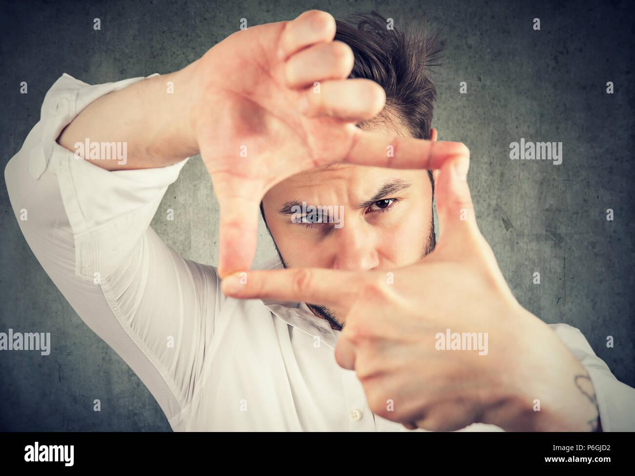 Junger Mann, einen Rahmen mit Fingern, Händen und Suchen durch Begrenzungen bei Camera auf grauem Hintergrund Stockbild