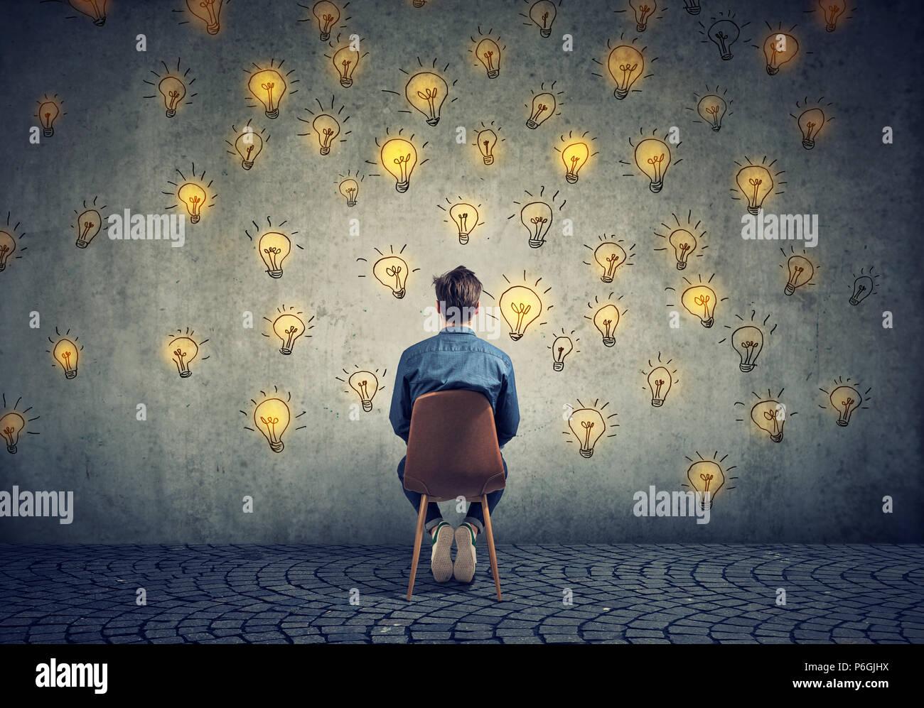 Mann sitzt auf einem Stuhl hat viele Ideen bei der Wall Entscheidungen suchen Stockbild