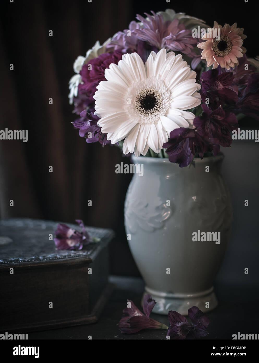 Dunkel gefärbte Blumen in einer Vase mit dunklem Hintergrund und gedeckten Farben. Stockbild