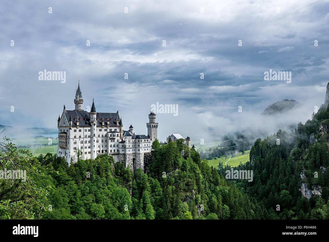 Schloss Neuschwanstein in Bayern mit Wolken am Himmel und ein wenig Nebel an einem sonnigen Tag Stockbild