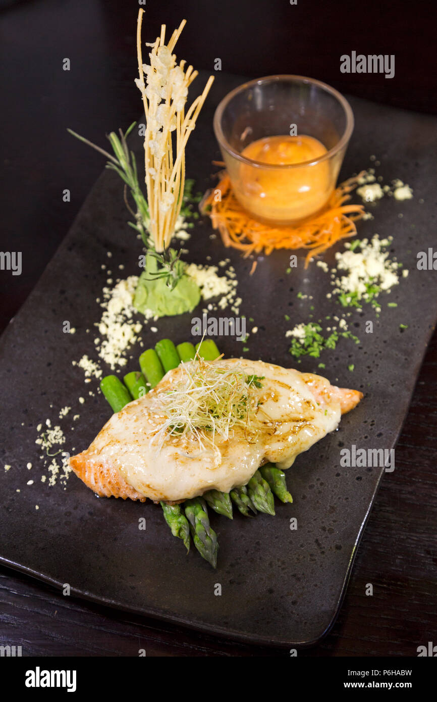 Gegrillter Lachs mit Spargel serviert. Es ist garniert und mit einem Glas Sriracha mayo serviert. Stockbild
