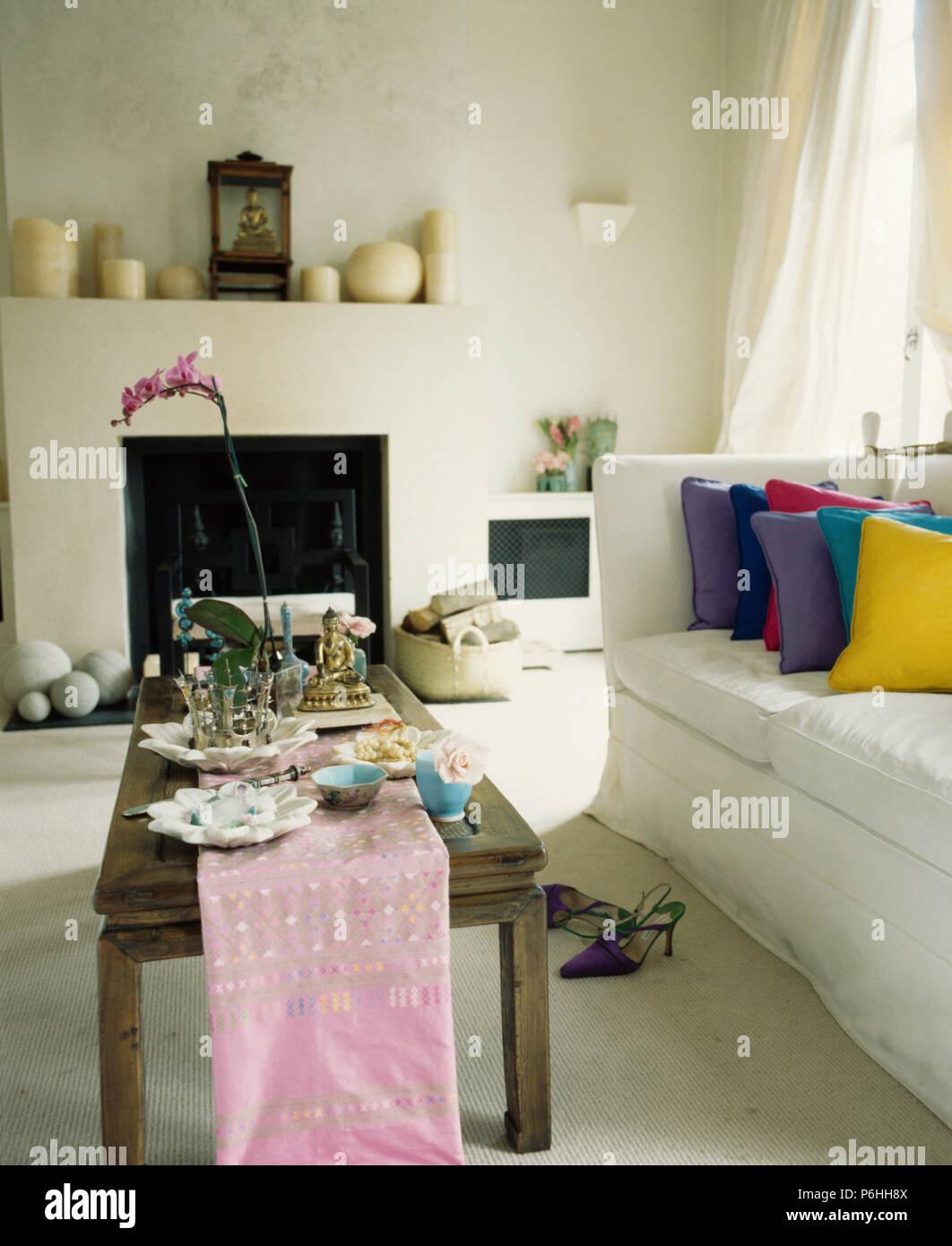 Rosa Läufer auf rustikalem Holz Tisch vor der weißen Sofa mit bunten ...