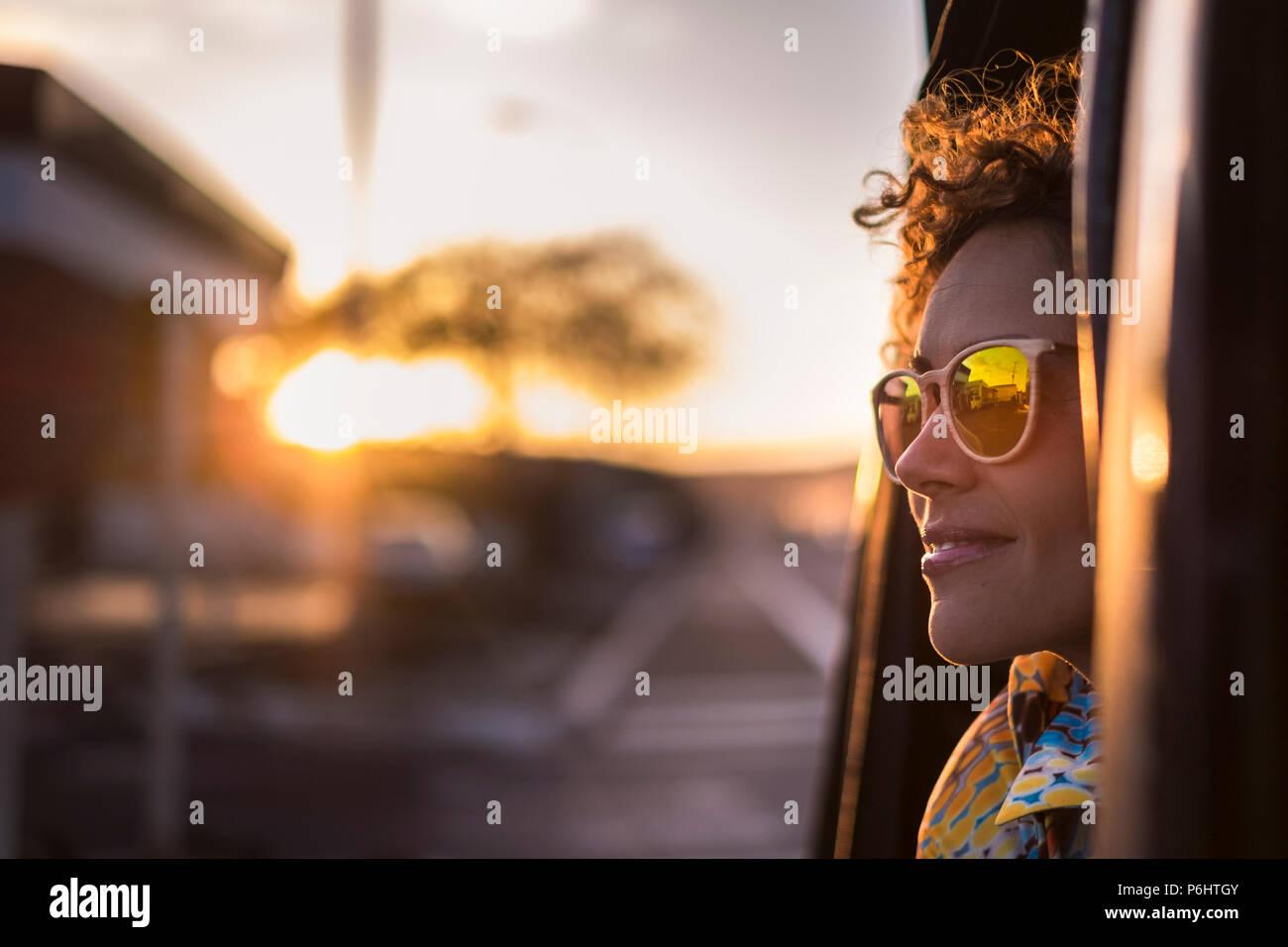 Schöne Frau reisen auf einem Auto außerhalb suchen und genießen Sie das Licht der goldenen Sonnenuntergang auf ihrem Gesicht. schön Lifestyle und friedlichen Emotionen Reisen a Stockbild