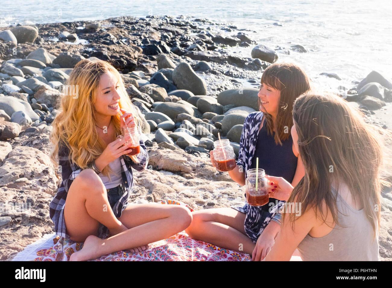 Gruppe von jungen Frauen Freund zusammen trinken Fruchtsaft auf einem Felsen am Strand auf Teneriffa. Beziehung für ein Team der Ferienhäuser und Glück zu EJOY. Stockbild