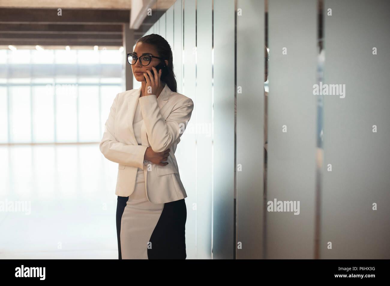 Junge brunette Business brillenbär Frau Gespräch per Handy. Stockbild