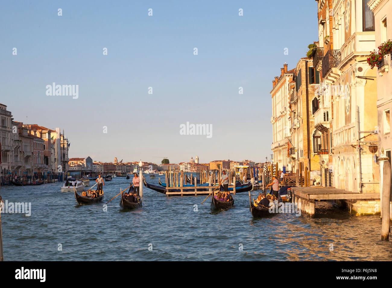 Touristen, romantischen Gondelfahrten bei Sonnenuntergang auf dem Canal Grande, Venedig, Venetien, Italien. Goldene Stunde mit Reflexionen. Stockbild