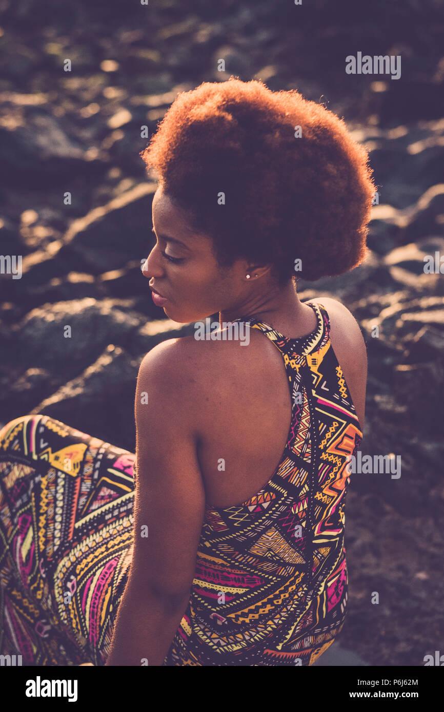 Attraktiv schön schwarzen Rasse Modell afrikanische Kleidung und Haare mit nackte Schulter setzen sie sich auf die Felsen defokussierten Hintergrund. Schönheit und Jugend co Stockbild