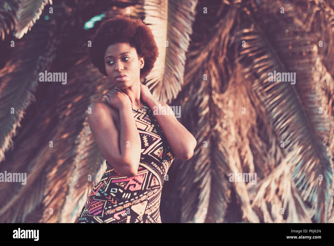 Schöne afrikanische schwarze Haut race Modell darstellen, in der Mode Stil mit farbigen Kleid mit einem tropischen Palmen natürlichen Hintergrund. Im Sommer Schönheit in Va Stockbild