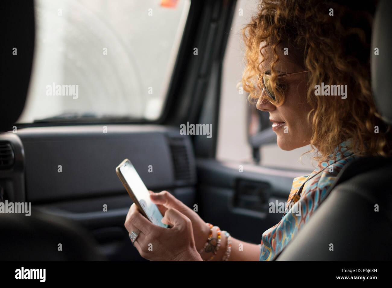 Schön, schöne junge Frau lächeln und die Nutzung von Mobiltelefonen durch Berühren des Bildschirms innerhalb des Autos während Reisen. moderne Konzept der Search Dinge und Kontakt Frie Stockbild