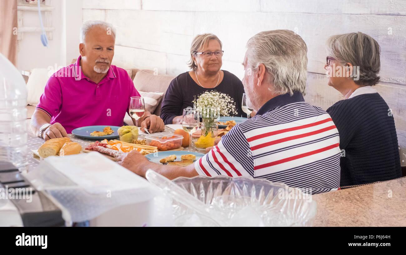Ältere Erwachsene zu Hause Mittagessen in Freundschaft und Glück. Alle ernsthaften sprechen über Probleme und Fragen. zwei Frauen und Teo Männer für zwei Fa Stockbild