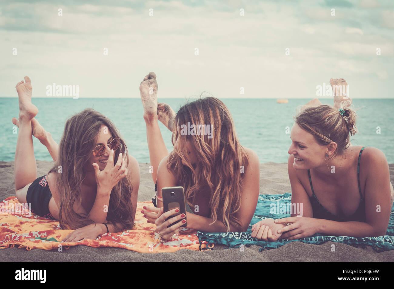 Drei schöne Mädchen mit Mobile Phone Technology Bilder am Strand entspannen und genießen Lifestyle und Urlaub Freizeitaktivitäten. outdoor Moderne Aktivitäten Stockbild